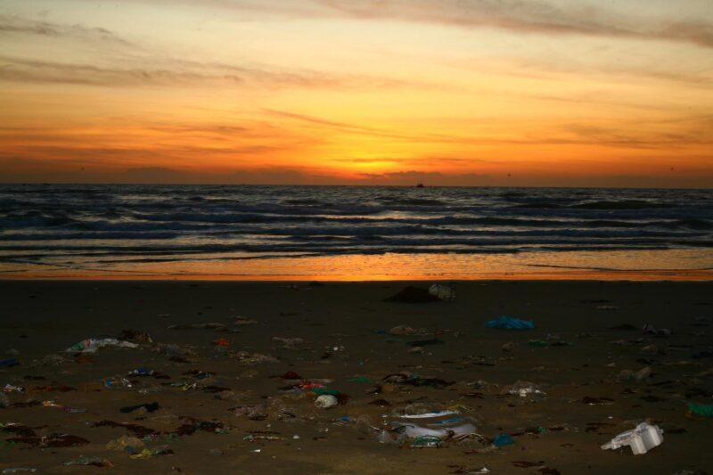 夕陽下充斥著海洋垃圾的沙灘