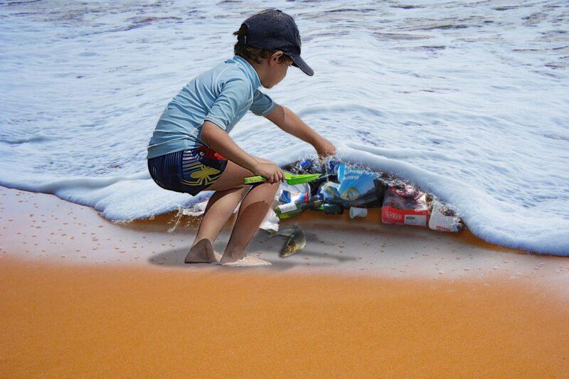 小男孩在撿拾海水裡的海洋垃圾